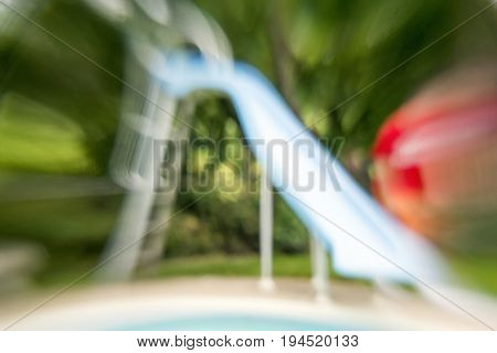Zoomed soft focus summertime background with pool slide and trees swimming and sport scene