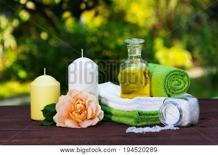 A pile of soft towels natural essential oil and sea salt. Roses and candles. Spa concept. Spa set in the summer garden.