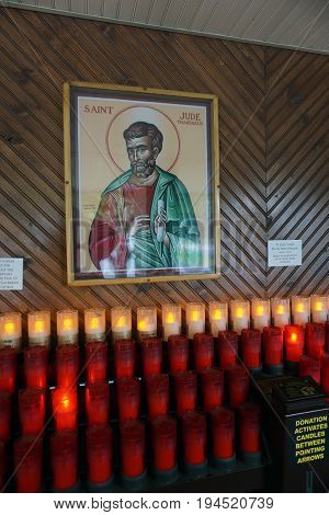 INDIAN RIVER, MICHIGAN / UNITED STATES - JUNE 18, 2017: Visitors and devotees may offer donations and light candles below a portrait of Saint Jude Thaddaeus, at the Cross in the Woods Roman Catholic National Shrine.