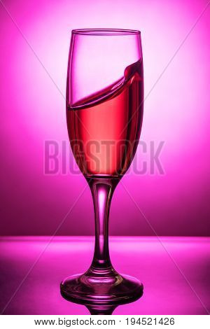 Splash of pink wine to the edge in a glass goblet on a pink background with a gradient spot