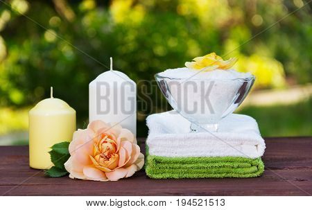 A bowl of fragrant sea salt a stack of soft towels candles and a fragrant rose. Spa set for relaxation.