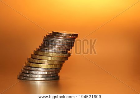 Falling Stack Of Coins On A Golden Background