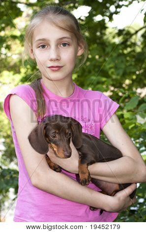 little blonde girl and a loving puppy dachshund poster