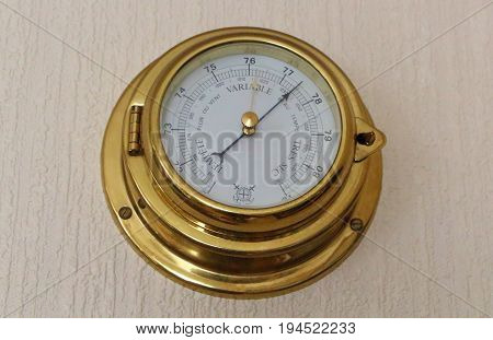 Golden barometer on a wall as decoration of a living room