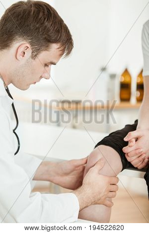 Doctor Examining Knee Of Young Teen Boy In Clinic