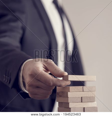 Toned Image Of A Businessman Placing Wooden Domino In A Tower