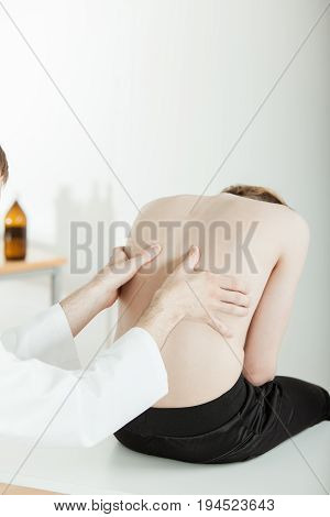 Doctor Examining Sore Back Muscles Of Teen Boy