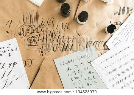 Calligraphy sheets, nibs, paper, ink on a kraft background. Lettering calligraphy workshop. learning calligraphy - paper with example and brush and ink. Concept hobby. top view, flat lay.