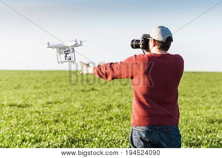 quadcopter summer outdoors, aerial imagery and recreation concept - photographer's SLR camera vs drone, cool electronic toy in hands of an adult boy, wonderful high-tech hobby for the male man