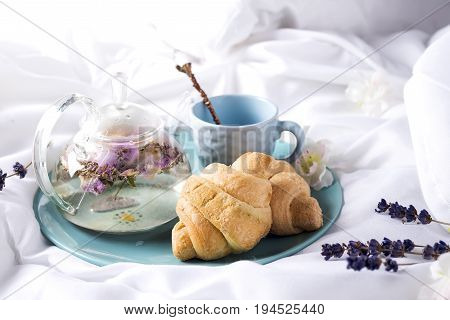 Breakfast in bed with tea, flower and croissant: teapot of flower tea with Fresh croissants on a plate . Valentine's day breakfast in bed, Mother's day or Women's day concept Flat lay