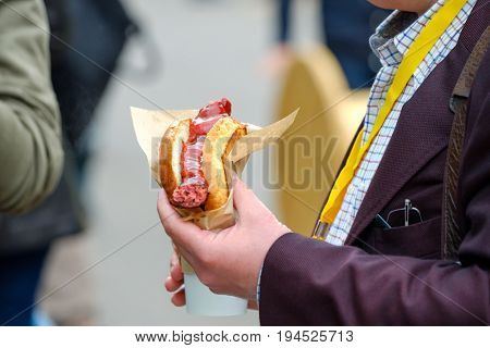 Man holds hotdog in the hand