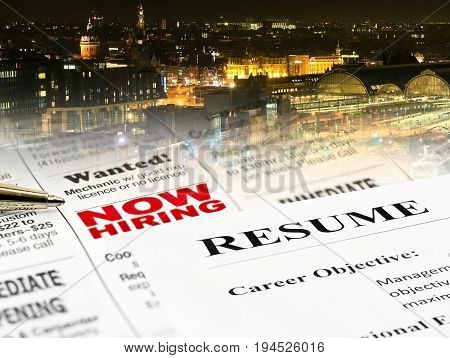 Closeup of Resume on Newspaper Career Opportunity Ad on night city background