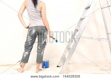 Low section rear view of young woman holding paintbrush against wall in house