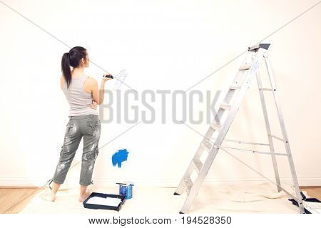 Full length rear view of young woman holding paintroller while analyzing paint on wall