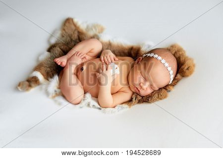 Newborn baby girl swaddled and laying on fur