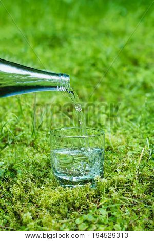 Pouring water from glass bottle into a glass on a grass in outdoor. Drinking water.