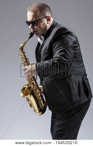 Music Concepts. Portrait of Mature Expressive Caucasian Saxophone Player in Sunglasses Playing the Saxophone in Studio Environment. Vertical Image Composition