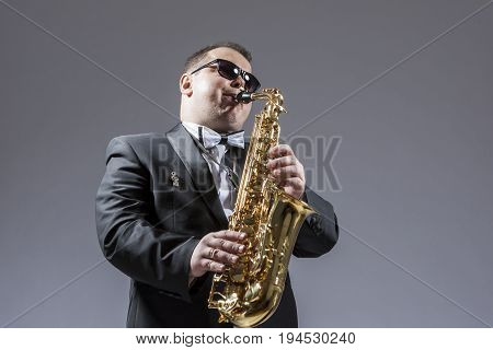 Music Concepts. Portrait of Mature Expressive Caucasian Saxophone Player in Sunglasses Playing the Saxophone in Studio Environment.Horizontal Image Composition