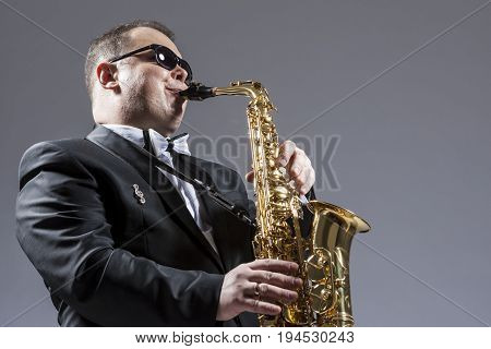 Music Concepts. Portrait of Mature Expressive Caucasian Saxophone Player in Sunglasses Playing the Saxophone in Studio Environment.Horizontal Image Orientation