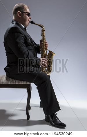 Music Concepts. Portrait of Mature Relaxed and Thoughful Caucasian Saxophone Player in Sunglasses Playing the Saxophone While Sitting on Chair in Studio Environment. Vertical Image