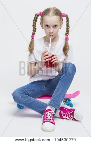 Kids Concepts. Portrait of Little Caucasian Blond Girl with Long Pigtails Posing With Pink Pennyboard and Drinking Red Juice with Straw. Against White. Vertical Image