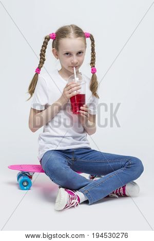 Kids Concepts. Portrait of Little Caucasian Blond Girl with Long Pigtails Posing With Pink Pennyboard and Drinking Red Juice with Straw. Against White. Vertical Shot