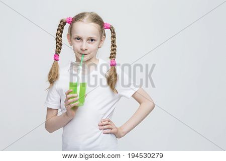 Portrait of Pretty Smiling Caucasian Blond Girl With Long Pigtails Holding Cup and Drinking Green Juice Through Straw. Horizontal Image Composition