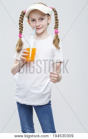 Portrait of Happy Smiling Caucasian Blond Girl in Visor Holding Cup of Juice and Showing Thumbs Up Sign.Vertical Image