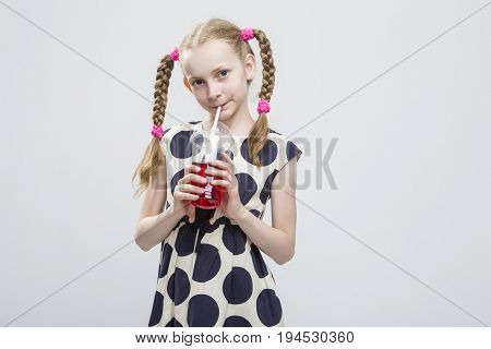 Portrait Of Smiling Caucasian LIttle Girl With Pigtails Standing in Polka Dot Dress with Cup of Red Juice. Against White. Drinking Through Straw. Horizontal Image