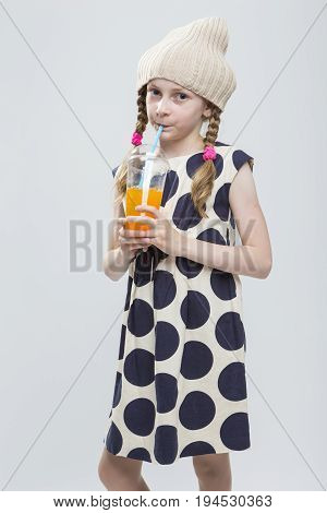 Portrait of Funny Caucasian Girl With Pigtails Posing in Warm Hat and Polka Dot Dress with Cup of Orange Juice. Drinking Through Straw. Against White. Vertical image