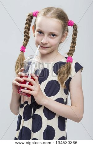 Kids Concepts. Closeup Portrait of Beautiful Caucasian Blond Girl With Pigtails Posing in Polka Dot Dress Against White. Holding Cup with Red Juice and Straw. Vertical Image