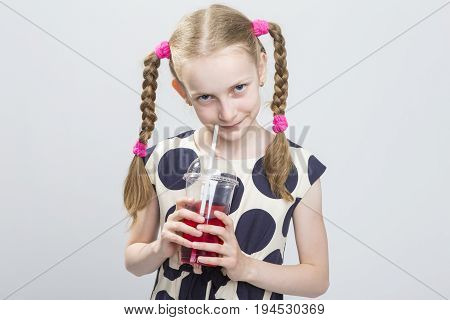 Kids Concepts. Closeup Portrait of Cute and Curious Caucasian Blond Girl With Pigtails Posing in Polka Dot Dress Against White. Holding Cup with Red Juice and Straw. Horizontal Image