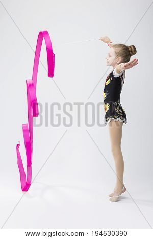 Professional Sport Concepts. Little Caucasian Female Rhythmic Gymnast In Professional Competitive Suit Doing Artistic Ribbon Spirals Exercises in Studio Against White. Vertical Image Orientation