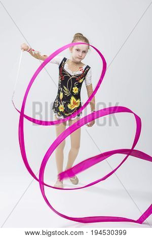 Sport Concepts. Little Caucasian Female Rhythmic Gymnast In Professional Competitive Suit Doing Artistic Ribbon Spirals Exercises in Studio On White. Vertical composition