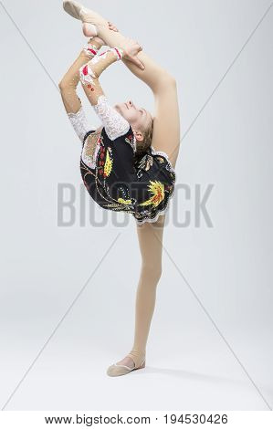 Sport concepts and Ideas. Young Caucasian Female Rhythmic Gymnast Athlete In Professional Competitive Suit Doing Vertical Split and Backbend While Posing in Studio Against White. Vertical Image
