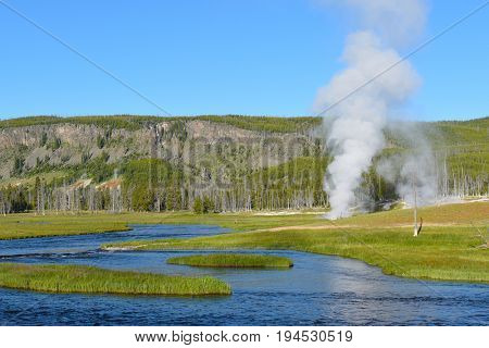 Thermal activity in Yellowstone National Park, Wyoming. Steam rises from a vent with mountains in the background and a lake in the foreground.