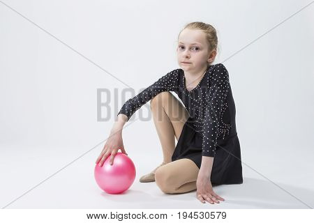 Caucasian Female Rhythmic Gymnast In Professional Competitive Black Sparkling Suit Posing With Ball in Studio On White.Horizontal Image