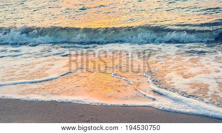 abstract background - orange sunrise reflecting off the waves crashing on the shore