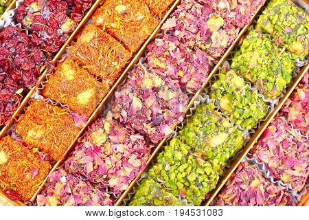 Arabic sweets with rose dry leaves and pistachios , close up shot