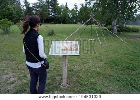 MACKINAW CITY, MICHIGAN / UNITED STATES - JUNE 18, 2017: A girl reads a sign describing a representation of a summer encampment of a band of Anishnaabek at the Colonial Michilimackinac State Park.