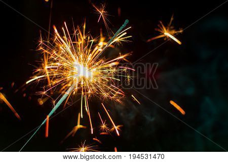 Warm orange sparkler burning at night with dark background