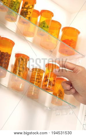Person's hand taking pill bottle from shelf