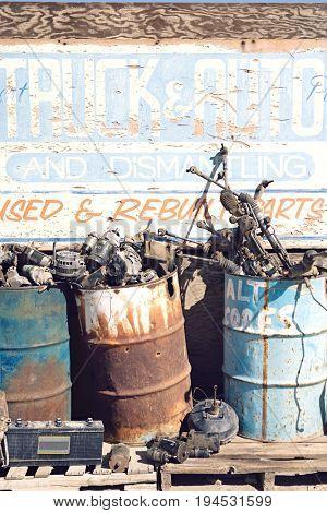 Rusty sign and barrels in junkyard
