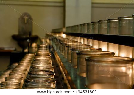 Rows of votive calendars lit by churchgoers in Catholic Cathedral