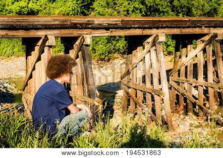 Young Man crouching with railroad bridge in background