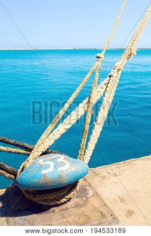 Closeup of a bollard with heavy duty mooring ropes in the dock at Limassol Cyprus