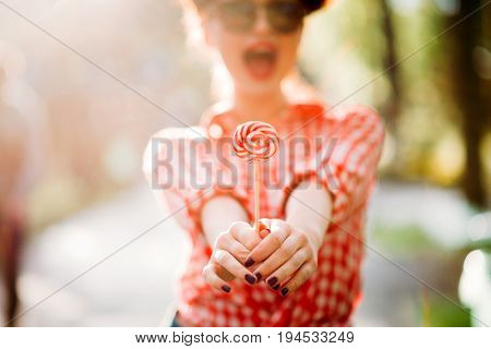 Sexy pinup girl holds out a hands with lollipop