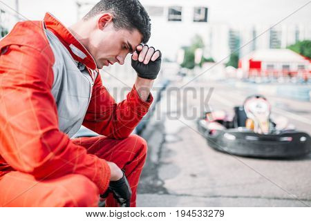 Karting racer sits on a tire, outdoor kart track