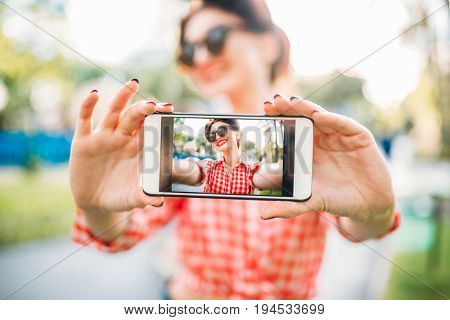 Pinup girl shows on phone outdoors selfie