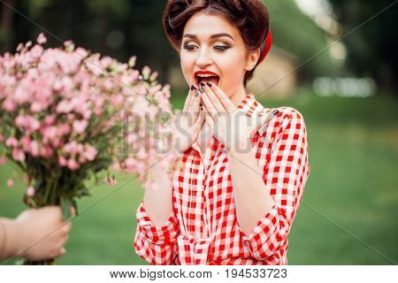 Glamour pinup girl takes gift a bouquet of flowers